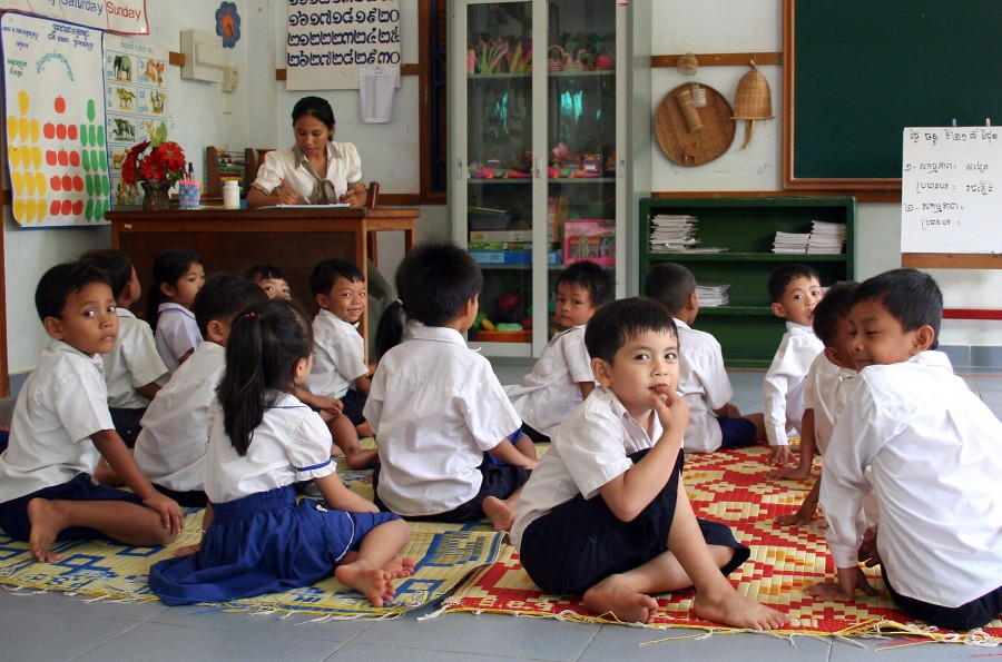Boys and girls in school uniforms sitting on the floor in the classroom. Teacher in background. Angkor-Siem Reap. Photographer: Mr. Axel Halbhuber